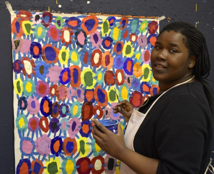 Photograph of Kwaga Sillingi looking at the camera whilst holding a paint brush and paint pot. She is stood in front of her painting.