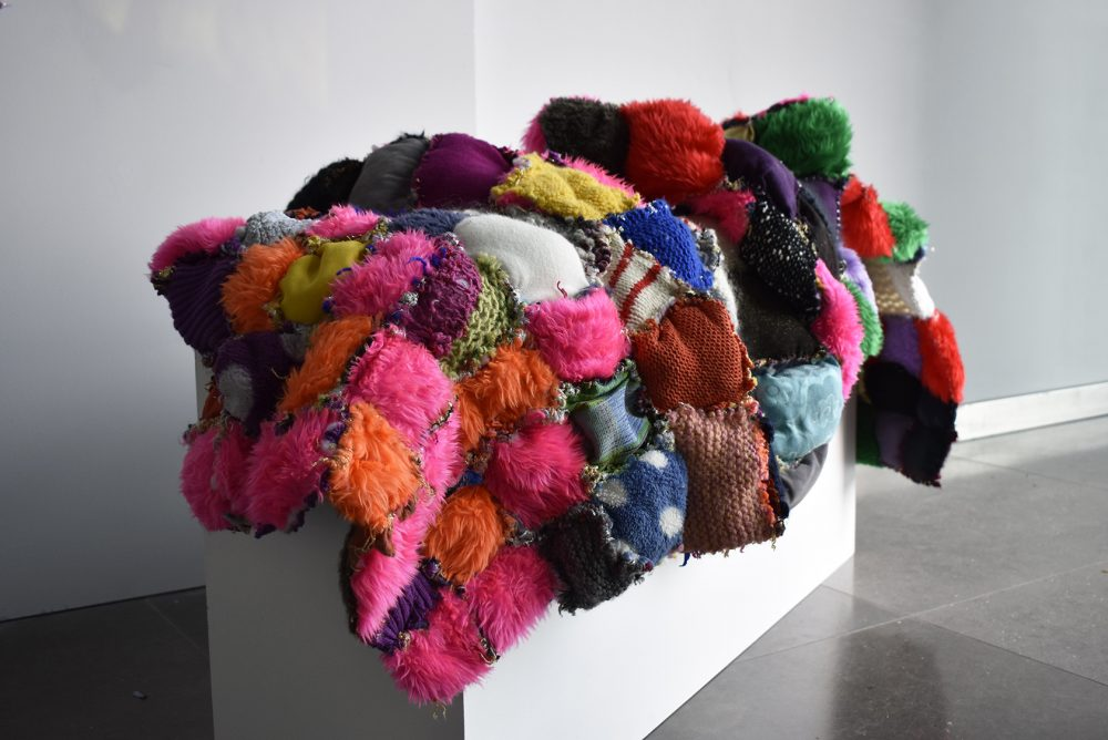Small squares of colourful fabric sewn together to create a large artwork that is draped over a white plinth