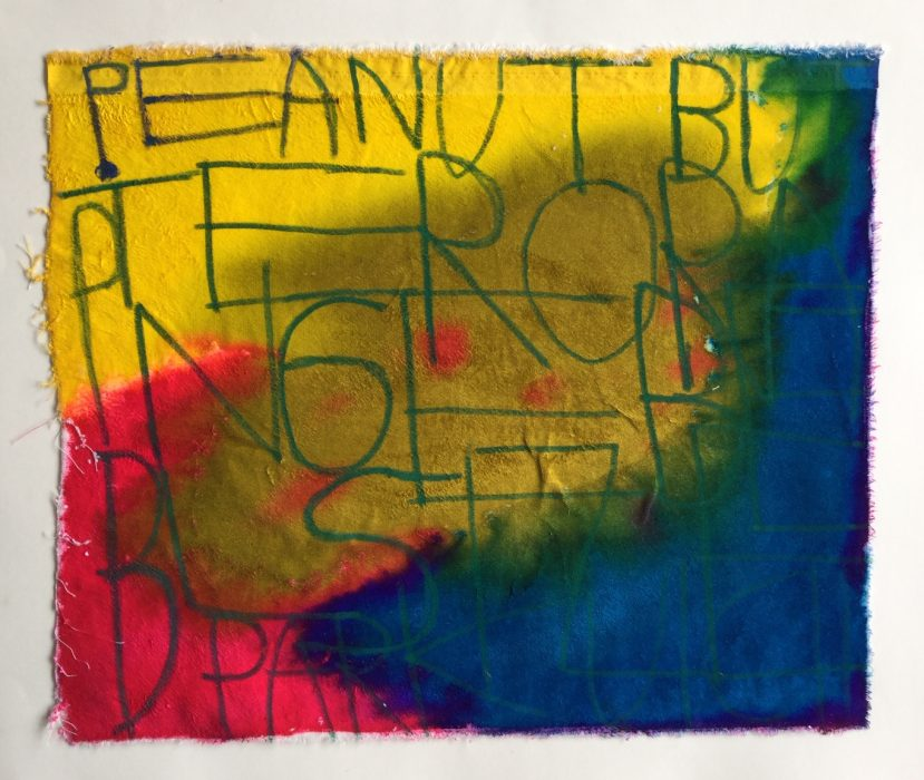 Rectangle shaped fabric coloured with bright inks that bleed into one another. Text written on top of the ink