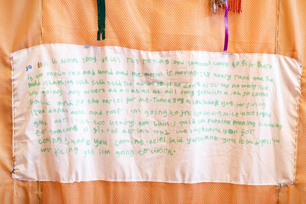 Fabric wall hanging by Andrew Omoding. Text is wirtten on the central panel of the work