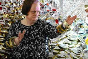 Linda Bell standing in front of her artwork made from metallic materials.