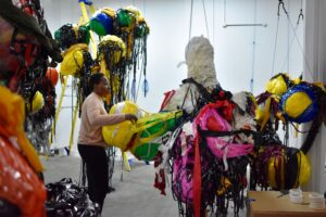 Nnena Kalu standing and building a boulder onto her suspended artworks make out of layers of tape, paper and plastic.