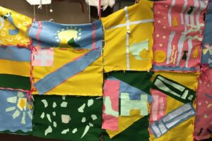 Artwork made by students on the SEN Schools programme. The artwork is a collage of yellow, blue, green and pink felt squares that have been collaged together