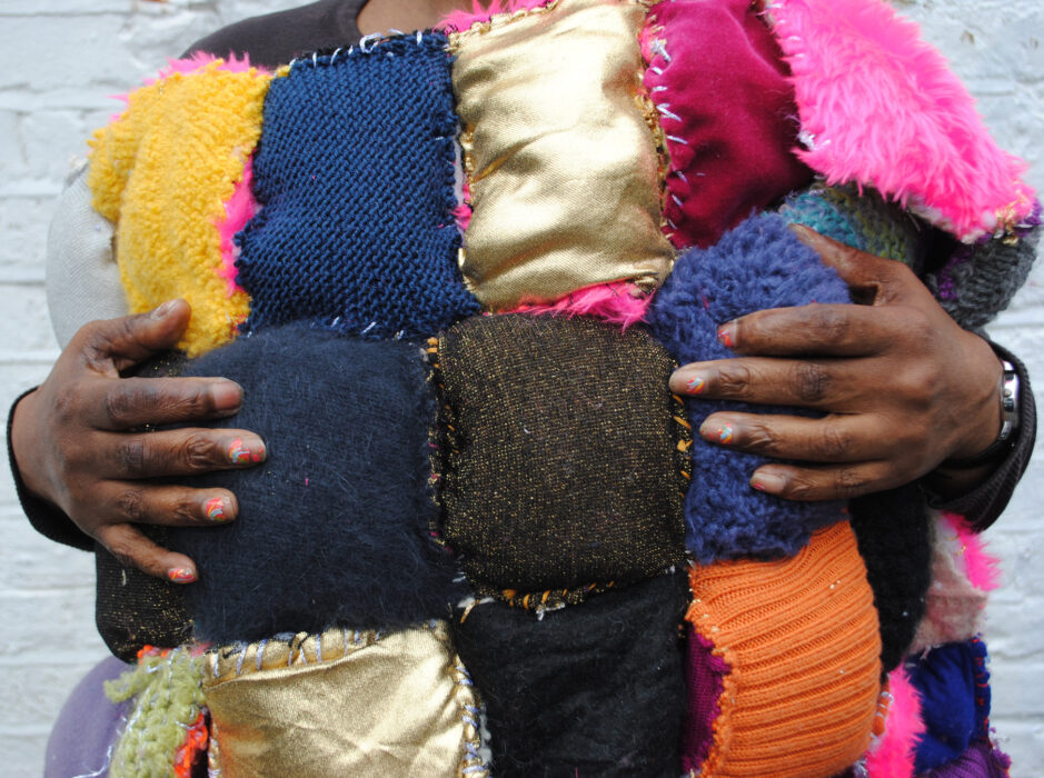 A photo of Lasmin Salmon's hands holding one of her quilts