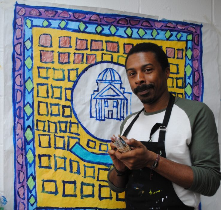 Thompson Hall standing in front of his painting. Thompson is wearing a black apron and is holding a selection of small paint brushes